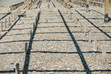 Close-up view of wood poles or sticks in pebble beach. Front view. - 192470662