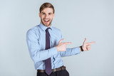 Young excited businessman pointing isolated on grey - 192473650