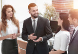 smiling business team talking, standing in office - 192475287