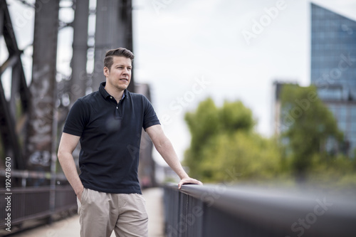 Portrait of a Handsome Man Posing on a City Bridge