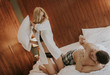 Quadro Playful young couple having pillow fight on bed in room