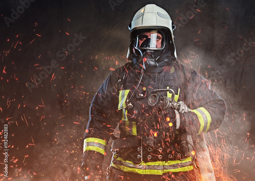 A firefighter dressed in a uniform in a studio. - 192482883