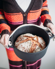 Woman with freshly baked homemade bread in a cast iron pot