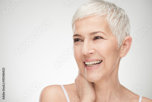 Leinwandbild Motiv Portrait of beautiful senior woman in front of white background.