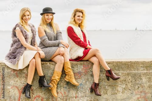 Three fashionable woman on pier