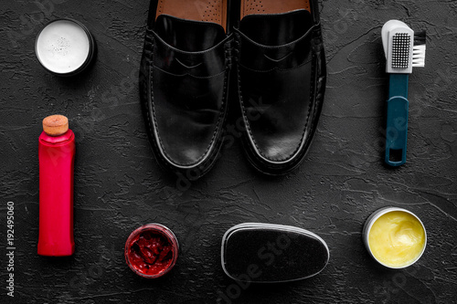 Clean shoes. Set of shoe care products. Polish, brushes, wax, sponge. Black background top view