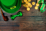 Saint Patrick's Day. Green hat of leprechaun, green bow tie, smoking pipe and gold coins on wooden background