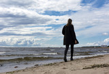 girl in black is on a sandy beach along the sea, the Gulf of Finland, cold water - 192505615