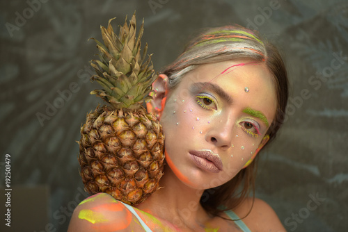 Young girl poses with pineapple fruit on shoulder - 192508479