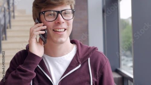 Smiling guy talking by phone, dolly footage