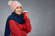 Quadro Smiling woman wearing warm clothes with winter hat holding red c