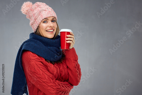 Fototapeta Smiling woman wearing warm clothes with winter hat holding red c