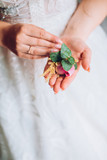 Gentle hand of the bride holding boutonniere for the groom. Bride holding a buttonhole - 192512034