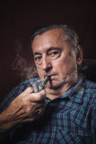 Classy senior elderly man smoking a pipe in his armchair, red background - 192512862