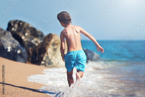 Foto Murales European boy is running along the sea shore.