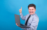 Business man is holding a laptop in his hands and showing his finger up. - 192516280