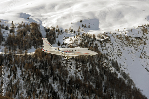 Fotobehang Donkergrijs A private jet landing to St Moritz airport in snowy mountains in the alps switzerland