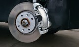 Close-up of a disc brake with caliper during tyre replacement. Car maintenance.