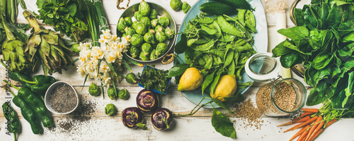 Wall mural Spring healthy vegan food cooking ingredients. Flat-lay of vegetables, fruit, seeds, sprouts, flowers, greens over white wooden background, top view. Clean eating, diet food concept