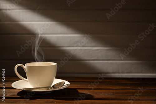 Sticker Cup of coffee with smoke on wooden background