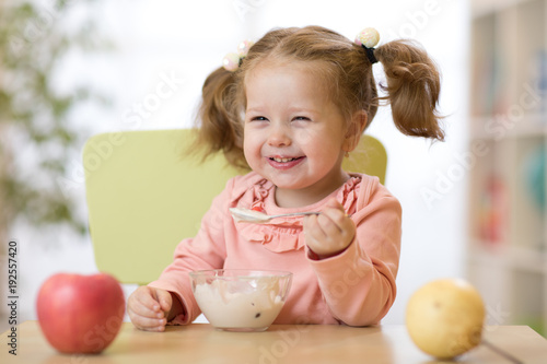 Cute child eating healthy food with the left hand at home - 192557420