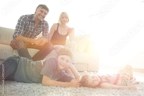 Foto Murales Portrait of children while parents sitting at sofa in living roo