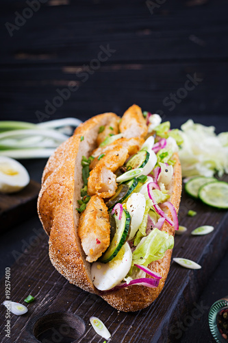 Fototapeta Baguette sandwich with fish, egg, pickled onions and lettuce leaves.