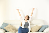 Happy woman raising arms and looking above on a couch - 192577011