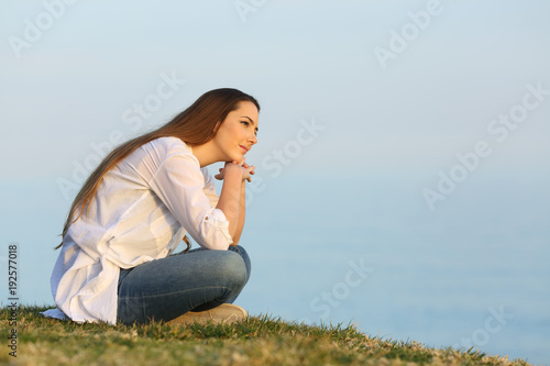 Relaxed woman thinking and looking away on the beach - 192577018