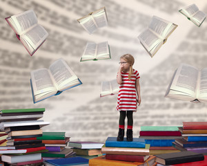 A small child with glasses standing among the books