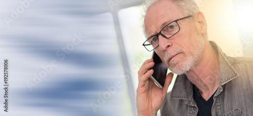 Portrait of mature man talking on phone, light effect