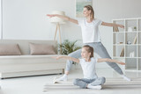 mother and daughter practicing yoga together - 192578625
