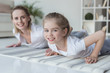 happy mother and daughter doing push ups together on yoga mats at home - 192579664