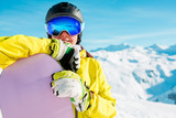 Portrait of smiling girl in helmet and mask with snowboard on background of snowy hills - 192584293