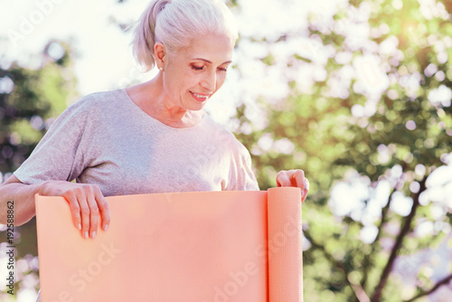 Time for relaxation. Smiling elderly woman unrolling the ground pad while standing in front of you and being concentrated