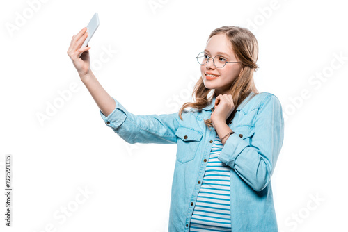 beautiful happy teenage girl in eyeglasses taking selfie with smartphone isolated on white