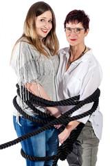 2 lächelnde, mit einem schwarzen Seil gefesselte, Frauen