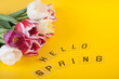 Words Hello spring laying on yellow background laying near spring bouquet