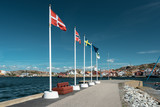 Flags of scandinavian countries waving on flagpoles on the shore. Scandinavian coastal city. - 192599238