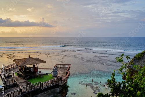 Foto op Aluminium Zee zonsondergang Multicolored sunset on Uluwatu island of Bali. Large clouds hung over the ocean. The house stands on the cliff face. Side view with copy space