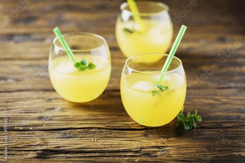 Glasses of orange cocktails with ice and mint