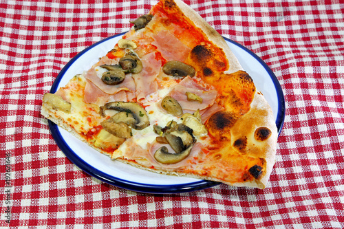 Keuken foto achterwand Pizzeria big slice of PIZZA at the Italian restaurant with red and white checkered tablecloth