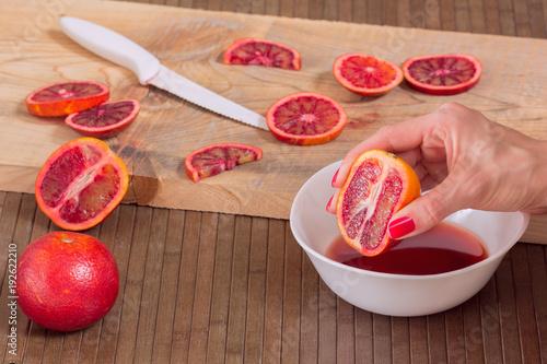 hand squeezes juice from Blood orange