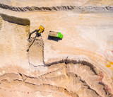 Aerial view of a excavator in the mine or construction site. Heavy industry and machinery. Industrial background on mining theme.  - 192654232