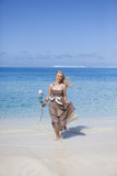 The beautiful woman with a rose runs on the edge of the sea on a beach. Polynesia - 192656402