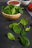 Italian cuisine. Mediterranean cuisine. Spinach leaves, tomato, oregano, tomato sauce and olives on table. Recipe Ingredients. - 192669605