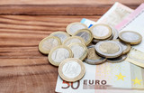 Euro bills and coins on the wooden table. Financial background. Copy space.