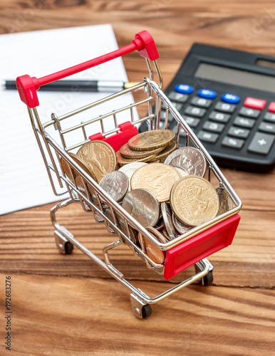 Shopping cart with coins, notepad and calculator on the table. Business concept. - 192683276