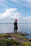 Young boy standing on the rock but the lake, Finland - 192685026