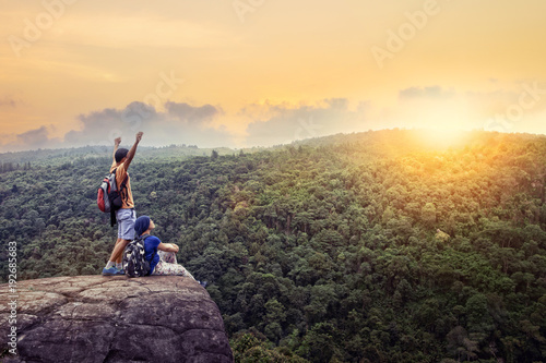 couples-of-traveling-man-and-woman-relax-on-top-of-high-mountain-with-beautiful-sunset-sky-behind-green-mountain